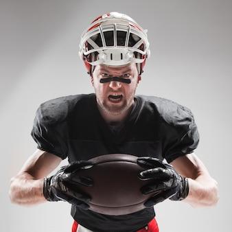 Giocatore di football americano in posa con la palla su sfondo bianco