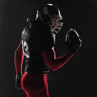 Giocatore di football americano in posa con la palla su sfondo nero