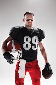 Giocatore di football americano in posa con la palla
