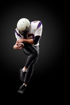 Giocatore di football americano in un salto con una palla sul nero