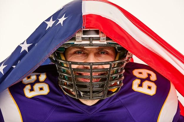 Giocatore di football americano in uniforme coperto con una bandiera americana
