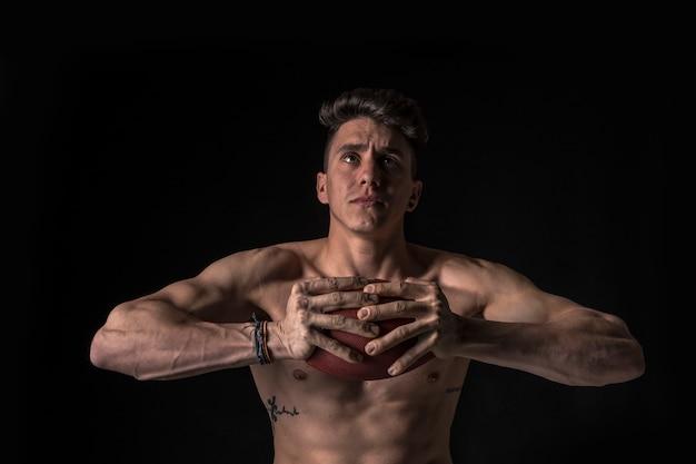 Giocatore di football americano nudo con gli addominali sul nero