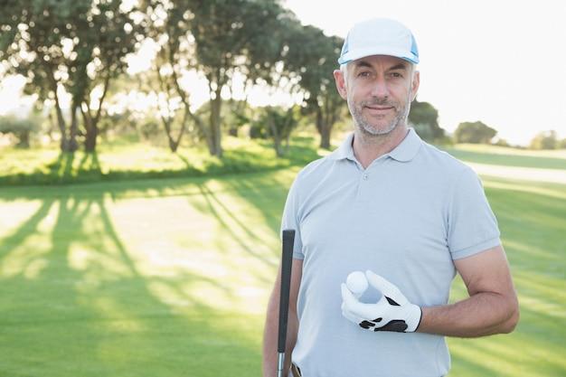 Giocatore di golf bello che sta con la palla da golf