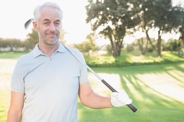 Giocatore di golf bello sorridente che guarda l'obbiettivo