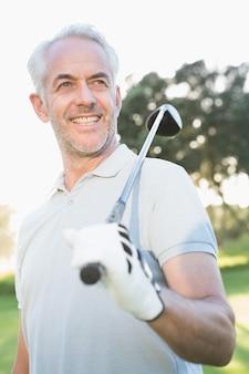 Giocatore di golf bello sorridente che osserva via