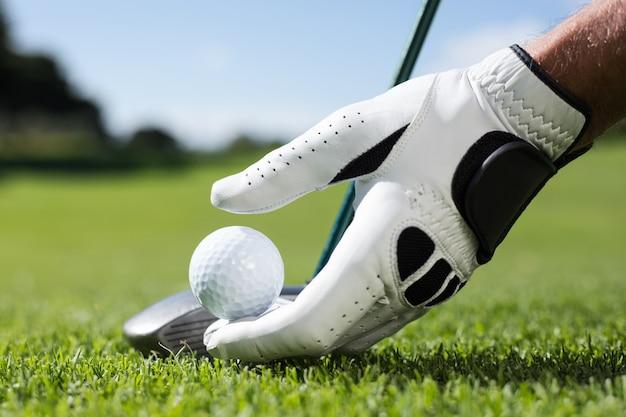 Giocatore di golf che dispone palla da golf sul tee