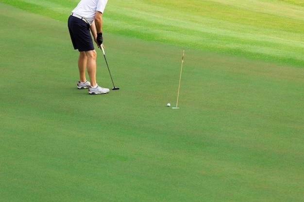 Giocatore di golf che mette la palla da golf sul golf verde