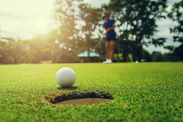 Giocatore di golf che mette la pallina da golf nel foro
