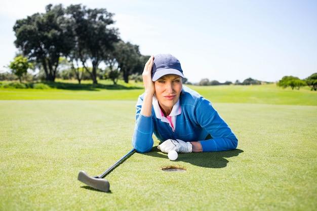 Giocatore di golf femminile che esamina la sua palla sul putting green