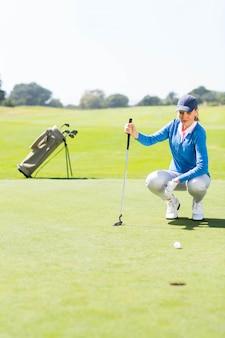 Giocatore di golf femminile che guarda la sua palla sul mettere verde