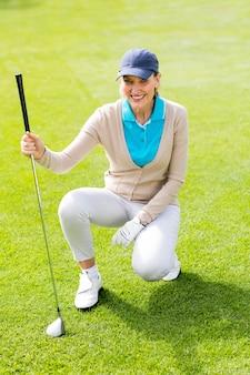 Giocatore di golf femminile che kneeing sul putting green