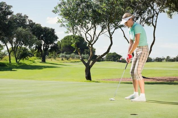 Giocatore di golf femminile che mette la sua palla