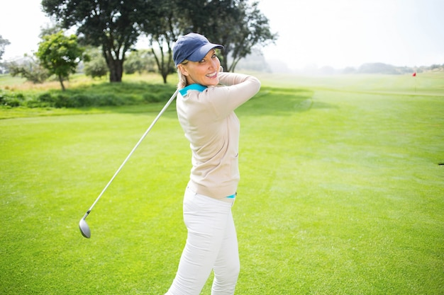 Giocatore di golf femminile che prende un colpo e che sorride alla macchina fotografica