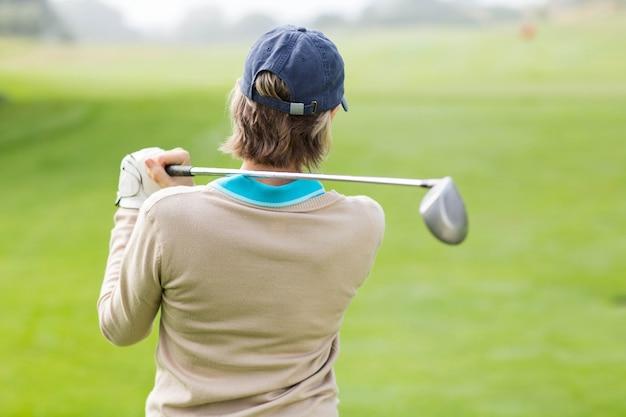 Giocatore di golf femminile che prende un colpo