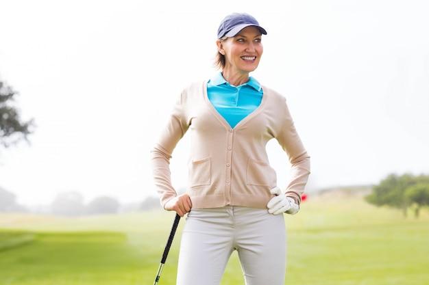 Giocatore di golf femminile che si leva in piedi con la mano sull'anca