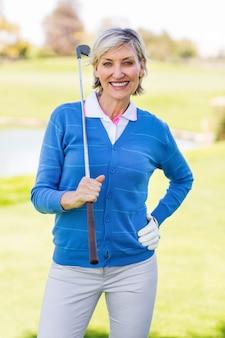 Giocatore di golf femminile che sorride alla macchina fotografica