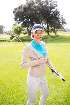 Giocatore di golf femminile che sta tenendo il suo club che sorride alla macchina fotografica