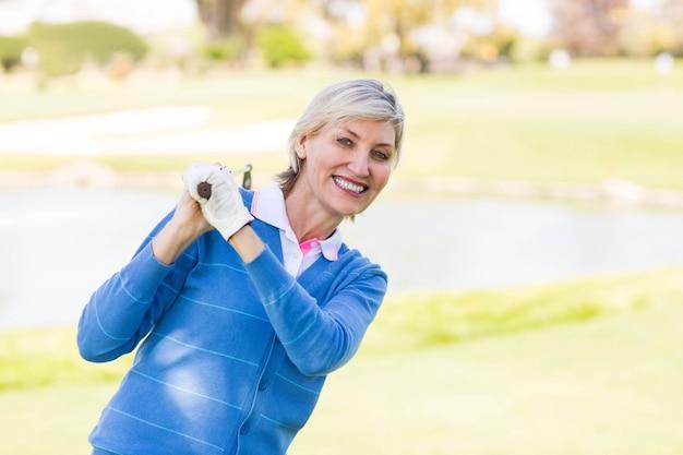 Giocatore di golf femminile che sta tenente il suo sorridere del club