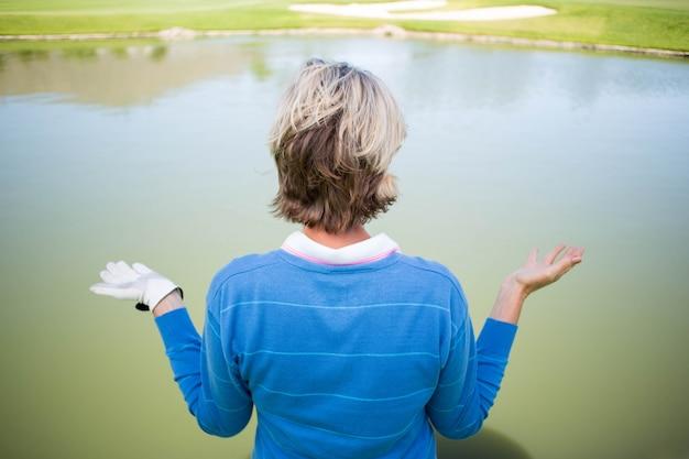 Giocatore di golf femminile confuso che esamina lago