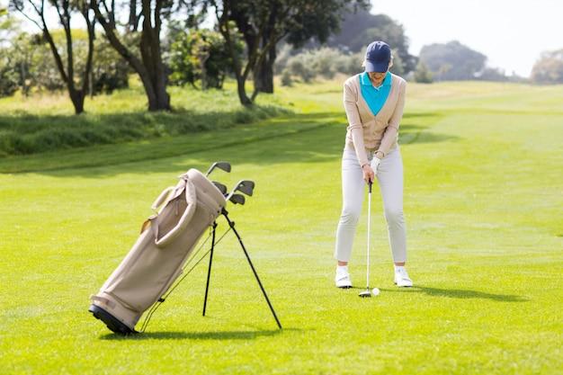 Giocatore di golf femminile di concentrazione che colloca sul tee fuori