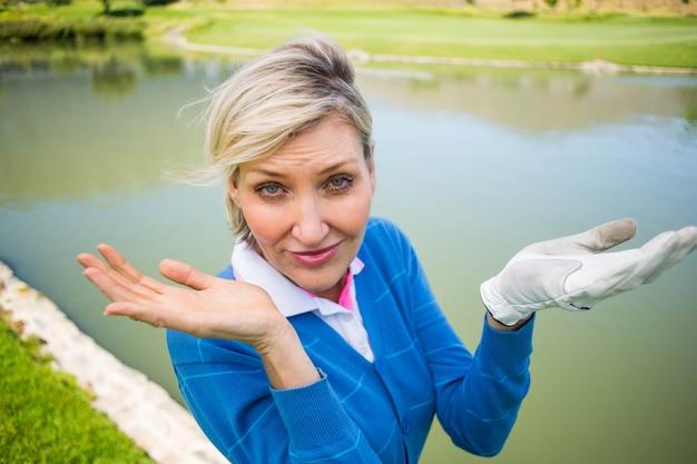 Giocatore di golf femminile preoccupato che cerca pallina da golf