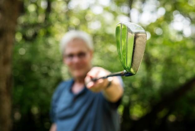 Giocatore di golf maggiore che tiene un golf club