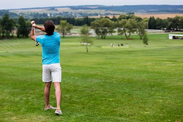Giocatore di golf maschio maschio di vista posteriore sul campo da golf professionale