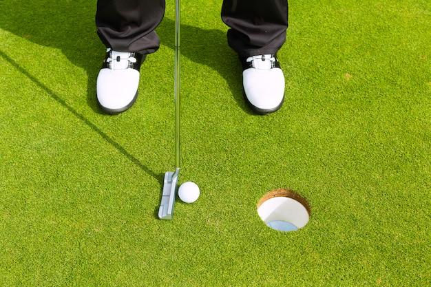 Giocatore di golf mettendo palla in buca