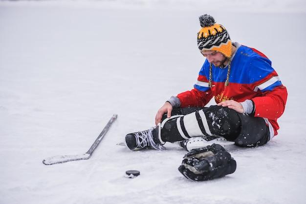 Giocatore di hockey perdente che si siede su quello del ghiaccio