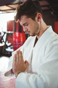 Giocatore di karate in posa di preghiera