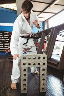 Giocatore di karate rompendo il blocco di cemento