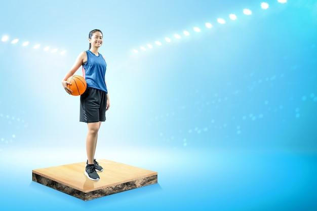 Giocatore di pallacanestro asiatico della donna che tiene la palla sulla sua mano
