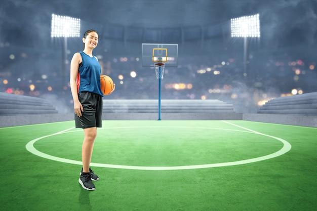 Giocatore di pallacanestro asiatico della donna che tiene la palla