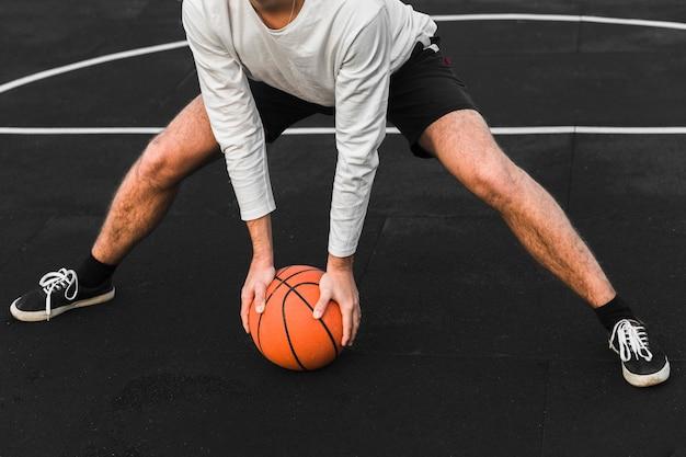 Giocatore di pallacanestro atletico che si esercita sulla corte