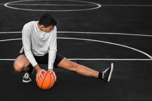 Giocatore di pallacanestro che allunga sulla corte