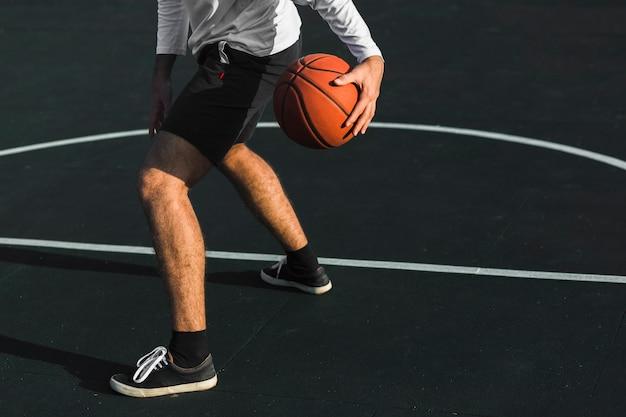Giocatore di pallacanestro che gioca sulla corte