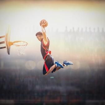 Giocatore di pallacanestro che segna una schiacciata atletica e d'azione
