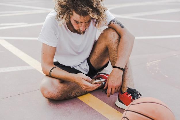 Giocatore di pallacanestro che si siede in tribunale facendo uso del telefono cellulare