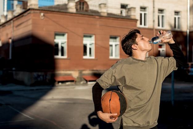 Giocatore di pallacanestro di vista frontale che idrata