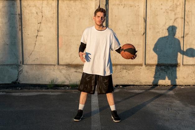 Giocatore di pallacanestro di vista frontale sulla corte urbana