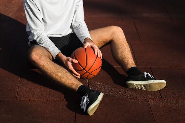 Giocatore di pallacanestro irriconoscibile che si distende sulla corte