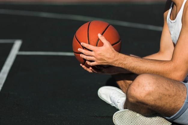 Giocatore di pallacanestro irriconoscibile che si siede sulla corte