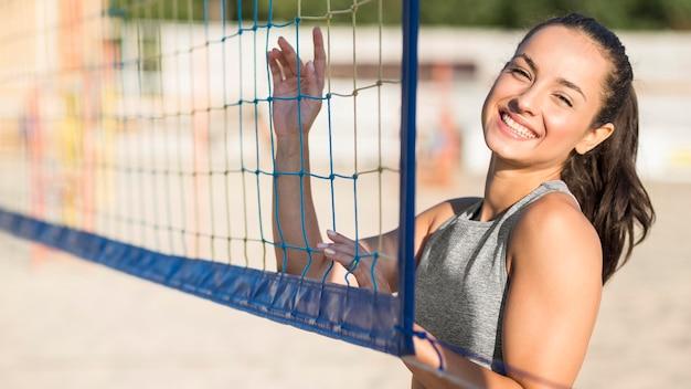 Giocatore di pallavolo femminile di smiley sulla spiaggia che posa con la rete