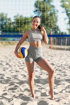 Giocatore di pallavolo femminile smiley sulla spiaggia in posa con la palla