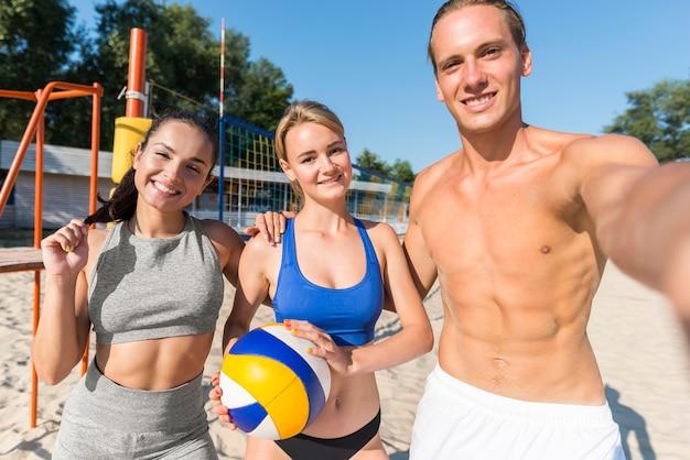 Giocatore di pallavolo maschio senza camicia che prende selfie con due giocatori di donne