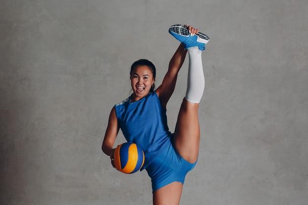 Giocatore di pallavolo sorridente della giovane donna asiatica in uniforme blu con la palla