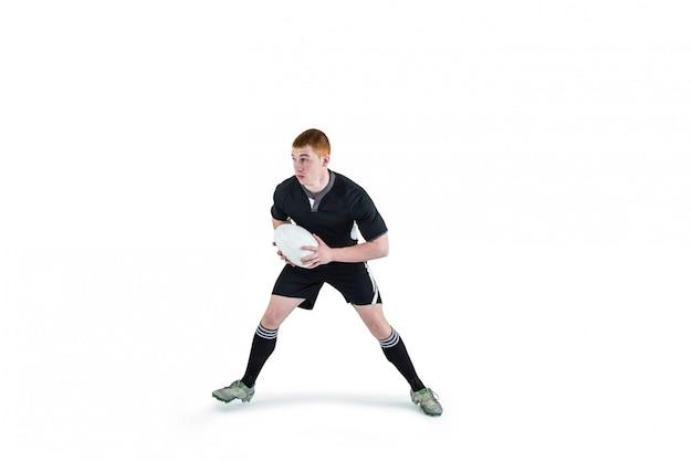 Giocatore di rugby che funziona con una palla da rugby