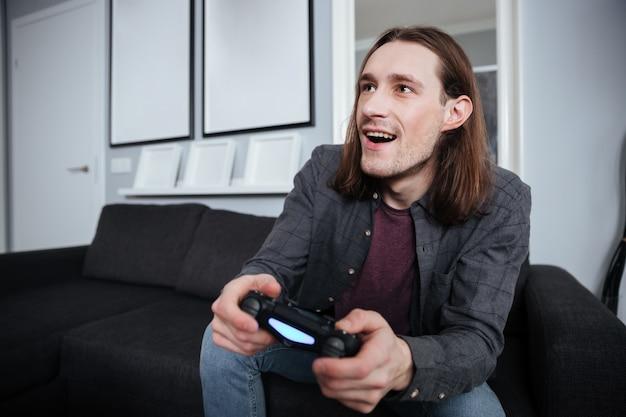 Giocatore di uomo felice seduto a casa al chiuso e giocare
