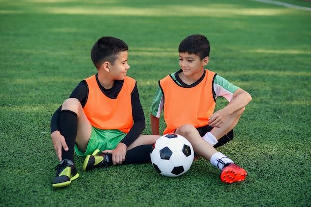 Giocatori di calcio adolescenti che riposa sull'erba artificiale