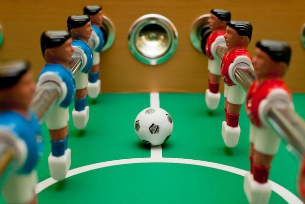 Giocatori di calcio balilla, primo piano con la palla.